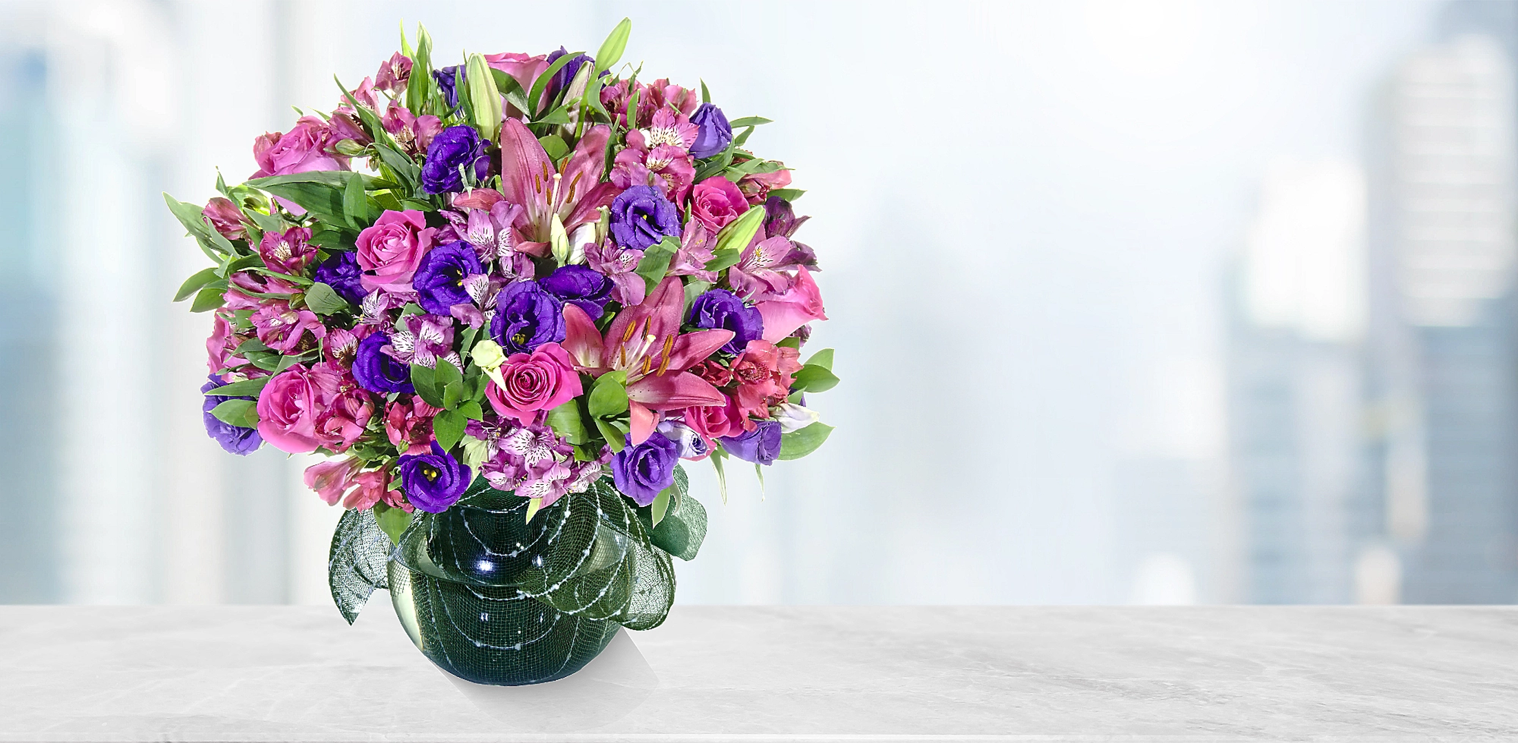 Espuma floral (3.0), Liliums Rosados (4.0), Lisianthus Morado (5.0), Astromelias (17.0), Decorado con papel arroz (1.0), Decorado con una malla simple (1.0), Ruscus (3.0), Rosa fucsia importada de tallo largo (12.0)